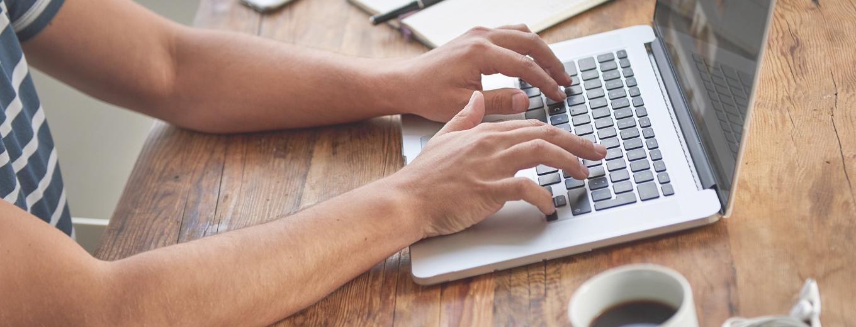 Мужчина за ноутбуком пишет текст