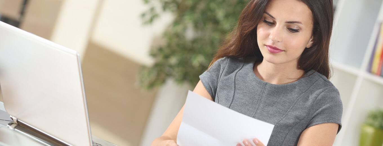 Девушка читает текст на бумаге